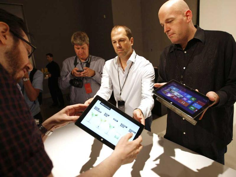 Microsoft representatives (R) show the new Surface tablet computer to members of the media as it is unveiled by Microsoft in Los Angeles, California. Reuters/David McNew