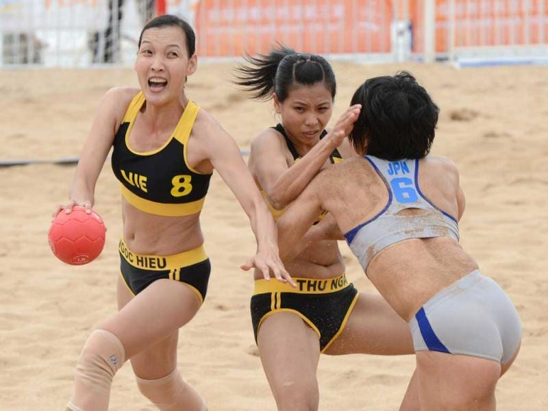 Ngoc Hieu Vo of Vietnam prepares to throw for goal as Erina Kutsukake of Japan attempts to block in their women's beach handball match at the 3rd Asian Beach Games in Haiyang, Shandong Province. Vietnam won 2-1. (AFP Photo)