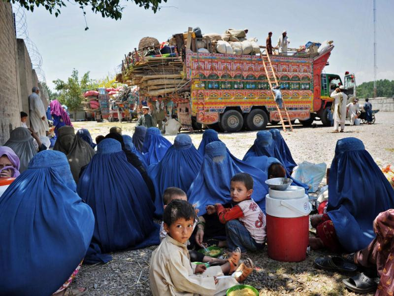 Afghan refugees sit in front of trucks at The United Nations High Commissioner for Refugees (UNHCR) registration centre on the outskirts of Peshawar, as they prepare to return to their home country after fleeing civil war and Taliban rule. AFP/A. Majeed