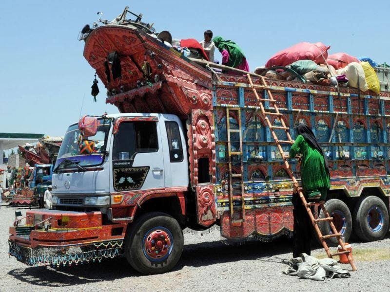 An Afghan refugee (C) climbs onto a loaded truck at The United Nations High Commissioner for Refugees (UNHCR) registration centre on the outskirts of Peshawar, as she prepares to return to her home country after fleeing civil war and Taliban rule. AFP/A. Majeed