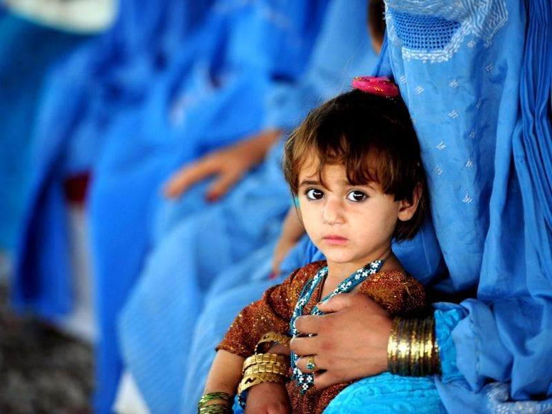 An Afghan girl sits with her mother at The United Nations High Commissioner for Refugees (UNHCR) registration centre on the outskirts of Peshawar, as they prepare to return to their home country after fleeing civil war and Taliban rule. AFP/A. Majeed