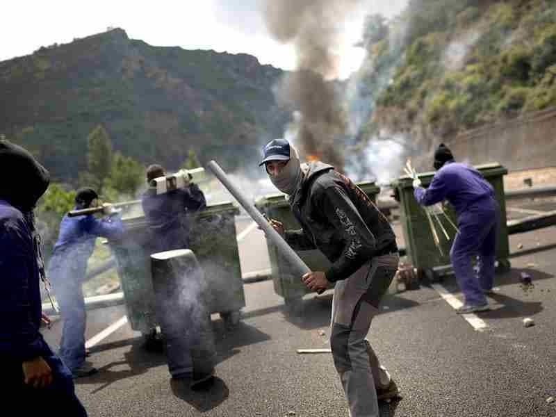 Miners fire handmade rockets at riot police officers as they defend their position after blocking a road in Cinera, near Leon, Spain. (AP Photo/Emilio Morenatti)