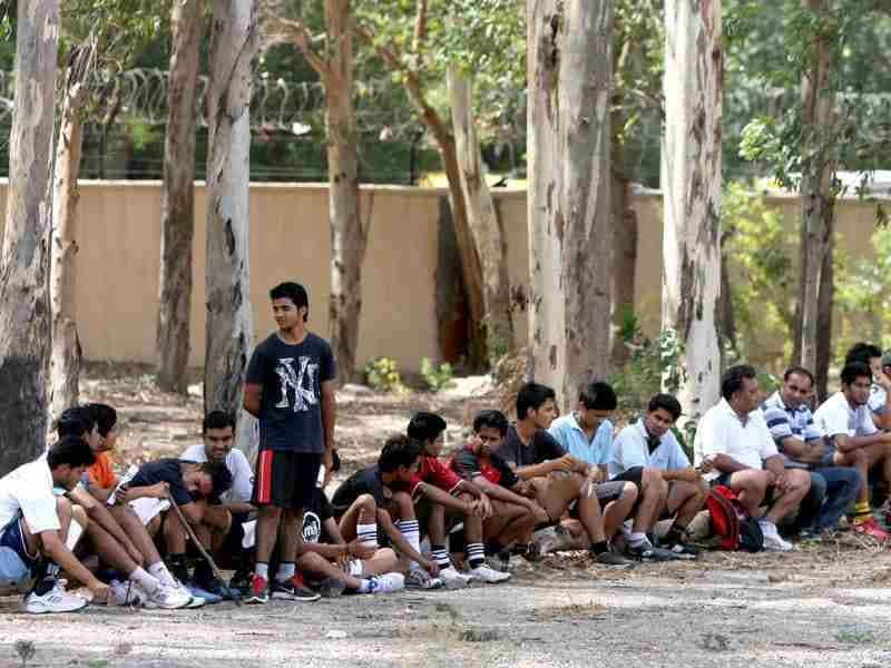 Aspirant students rest under tree shades during the Fitness trail test for admission at Shri Ram College of Commerce in New Delhi. HT/M Zhazo