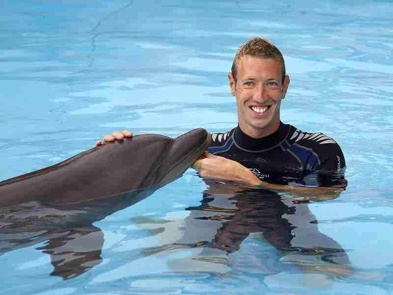 French Olympic champion swimmer Alain Bernard poses with a dolphin at the Marineland aquatic park in Antibes. Reuters/Eric Gaillard