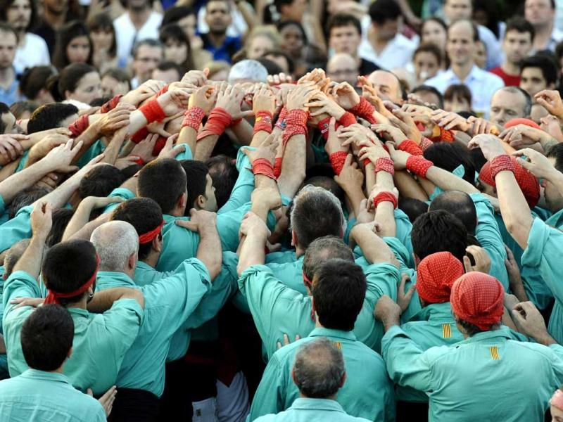 The 150 member Castellers de Vilafranca gather hands before attempting a new world record by building the first eight-level human tower or castell ever assembled on a rooftop in New York City. AFP/Timothy A Clary