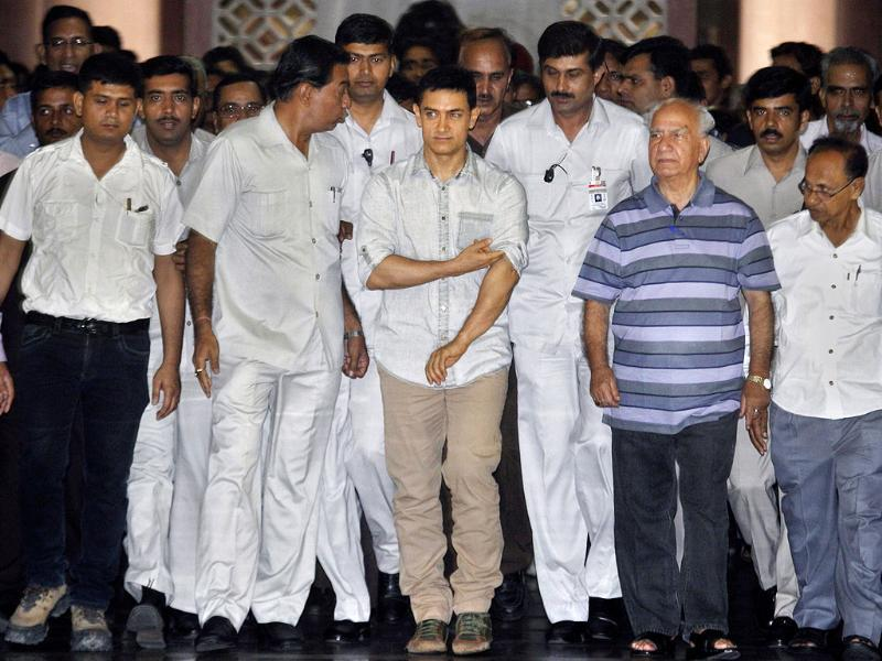 Bollywood actor Aamir Khan walks with Shanta Kumar, a Rajya Sabha MP, second from right, as he arrives to address the media at Parliament house in New Delhi. Khan met a parliamentary panel examining foreign investment in the pharmaceuticals sector and pitched for generic medicine, which could be sold cheaper to the poor. AP/Manish Swarup