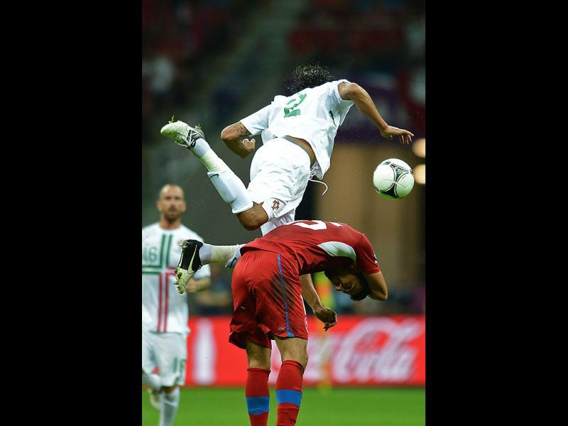 Czech forward Milan Baros (down) vies with Portuguese defender Bruno Alves during the Euro 2012 football championships quarter-final match the Czech Republic vs Portugal at the National Stadium in Warsaw. AFP/Francisco Leong