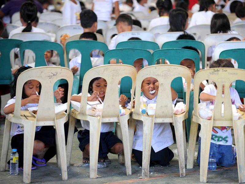 Preparatory and elementary students eat packaged meals during a feeding program at a slum area in Manila. The local government distributed food to the children during the 441th anniversary of the capital city Manila. AFP/Noel Celis