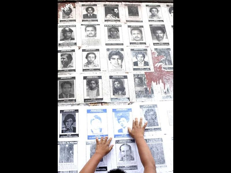 A man sticks portraits of people disappeared in the 80's on a wall in front of the National Congress in Guatemala City. According to human rights groups, more than 40.000 were disappeared by army dead squads during 36 years of internal conflicts. AP Photo/Rodrigo Abd