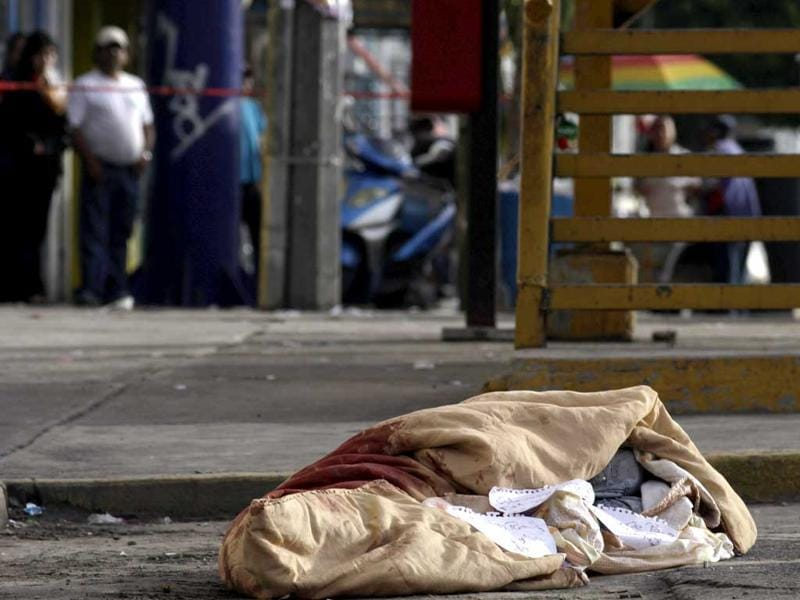 The slain body of a man wrapped in a blanket is pictured at a crime scene in Temixco, on the outskirts of Cuernavaca. According to local media, the man had signs of torture and threat messages were left alongside the body. REUTERS/Margarito Perez