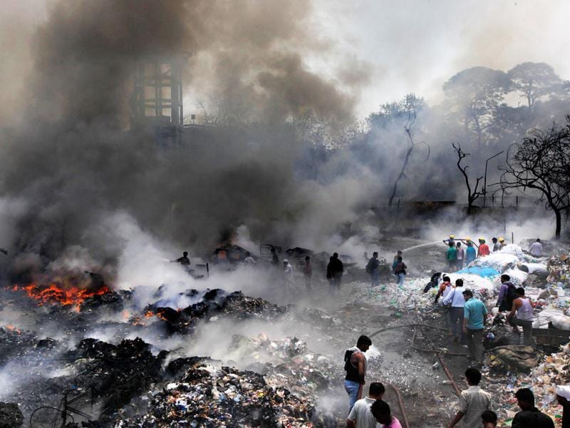 Residents and fire fighters try to douse down the fire at a scrap yard in New Delhi. AP Photo/Manish Swarup