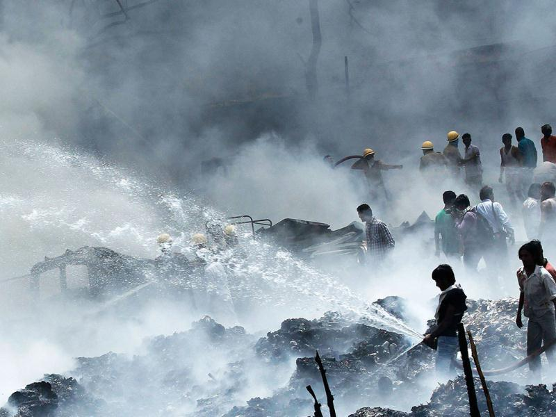 A local resident tries to extinguish a fire from a slum area in New Delhi. Reuters photo/Adnan Abidi