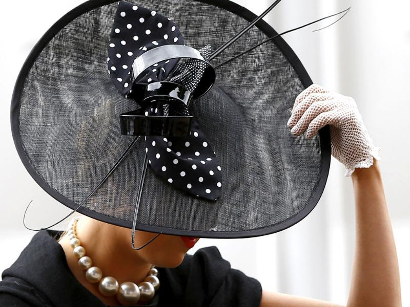 Blair Soczewko holds onto her hat as she arrives on a windy day for the fourth day of Royal Ascot horse race meeting at Ascot, England. (AP Photo/Alastair Grant)