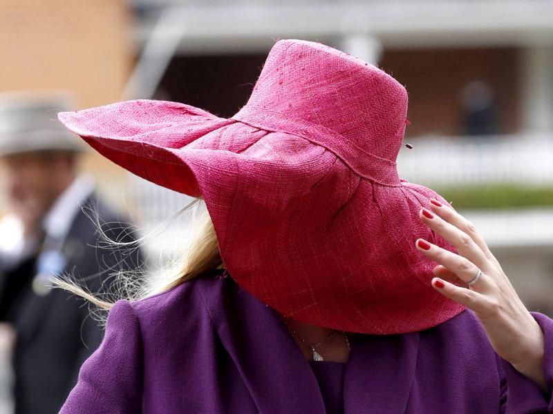 A race goer struggles to keep her hat on in strong winds on the fourth day at Royal Ascot, southwest of London. (Reuters/Stefan Wermuth)