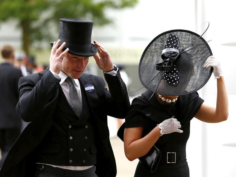David Jordan and Blair Soczewko hold onto their hats as they arrive on a windy day for the fourth day of Royal Ascot horse race meeting at Ascot, England. (AP Photo/Alastair Grant)