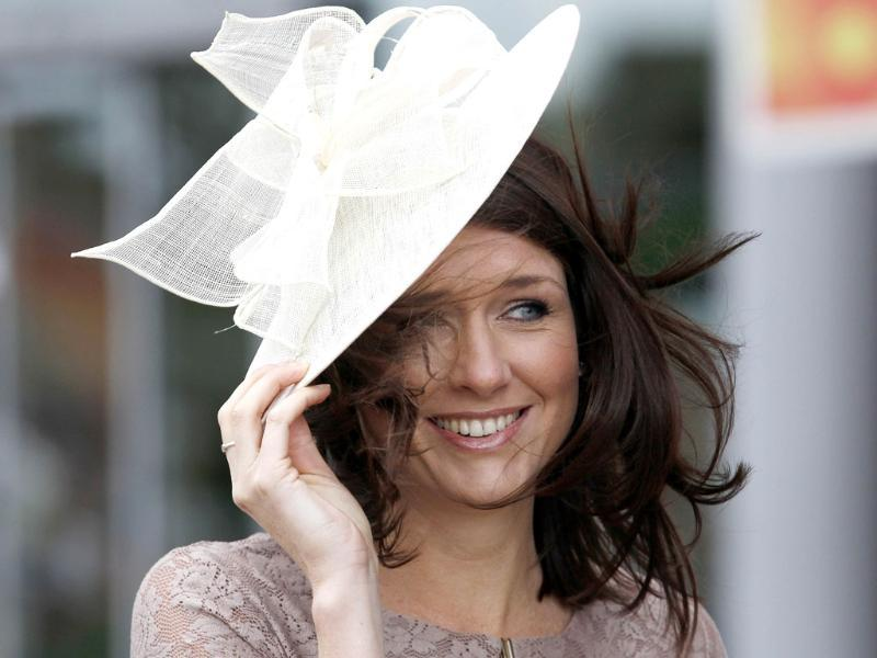 A race goer struggles to keep her hat on in strong winds on the fourth day at Royal Ascot, southwest of London. (Reuters/Andrew Winning)