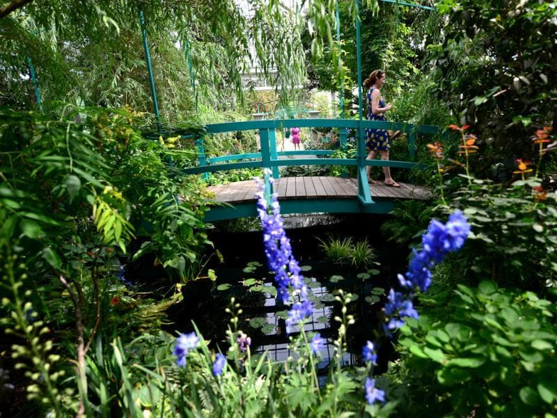 A visitor walks on a replica of French painter Claude Monet's Japanese footbridge arching over a water lily pool encircled by willow trees and flowering shrubs at his house in Giverny during 'Monet's Garden' exhibition, at the New York Botanical Garden. AFP/Emmanuel Dunand