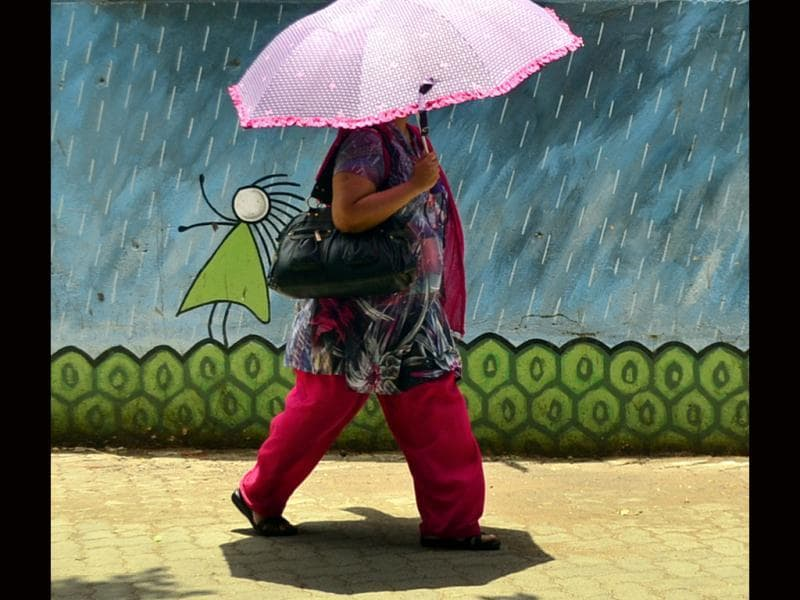 With temperatures soaring, a woman walks with an umbrella to shield herself from the scorching heat, in the backdrop of a wall-painting of rain at Versova, Andheri West, in Mumbai. HT/Vidya Subramanian