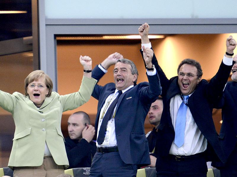 German Chancellor Angela Merkel, German football association president Wolfgang Niersbach and German Interior Minister Hans-Peter Friedrich celebrate after Philip Lahm scored against Greece during the Euro 2012 football championships quarter-final match Germany vs Greece at the Gdansk Arena.  AFP/Fabrice Coffrini