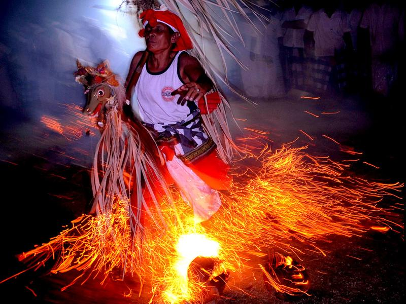 A Balinese man walking across a fire during the Sanghyang jaran ritual dance performed at a temple in Kuta, Indonesia's resort island of Bali. Sanghyang jaran is a dance performed by boys who ride coconut palm hobbyhorses in and around a fire. AFP/Sonny Tumbelaka