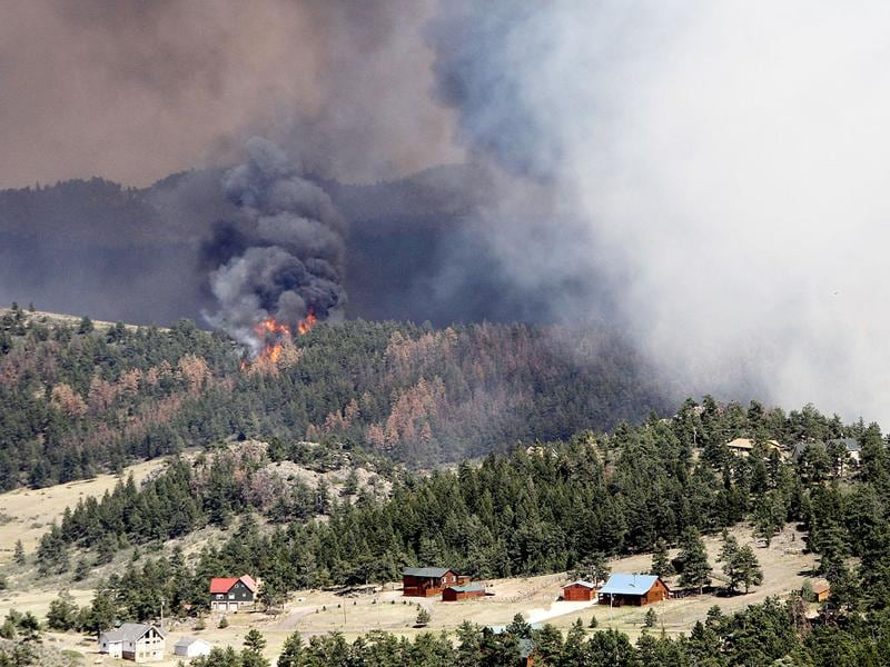 Fire burns behind homes north of Poudre Canyon in the Glacier View area near Livermore, Colo. The fire is burning on more than 68,000 acres west of Fort Collins and has destroyed at least 189 homes. AP Photo/Ed Andrieski