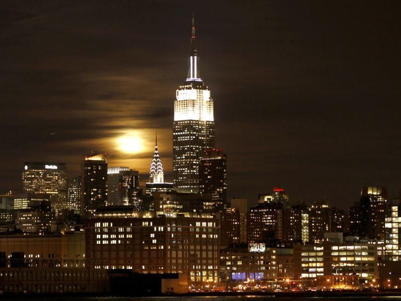 A full moon rises behind the Empire State Building and the Chrysler Building over the skyline of Manhattan in New York. Reuters/Gary Hershorn