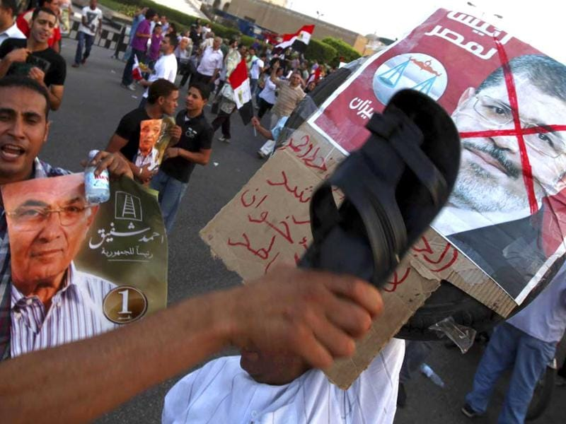 A supporter of former prime minister and current presidential candidate Ahmed Shafik hits a defaced poster of the Muslim Brotherhood's presidential candidate Mohamed Morsy with shoes during a rally in support of the Supreme Council for the Armed Forces (SCAF) at Nasr City in Cairo. REUTERS/Amr Abdallah Dalsh