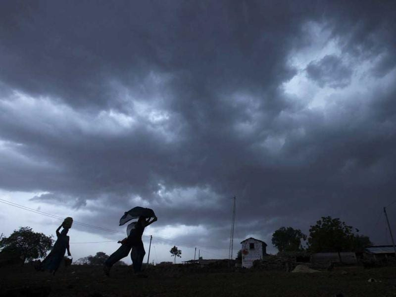 A girl runs for cover as monsoon clouds gather over Meerwada village in Guna district in the central Indian state of Madhya Pradesh. Reuters/UNI