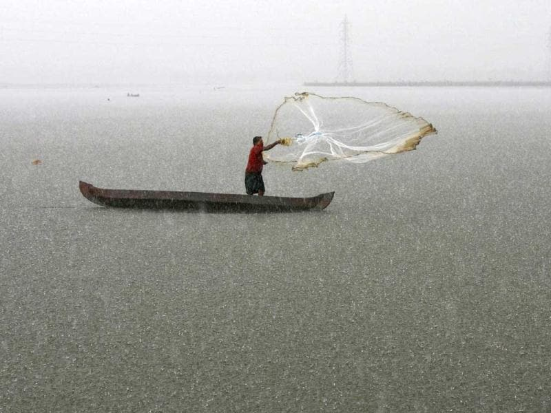 Man casts his fishing net into the waters of a fish farm during a heavy rain shower on the outskirts of Kochi. The India Meteorological Department (IMD) has forecast average rainfall for the whole June to September. Reuters/Sivaram V