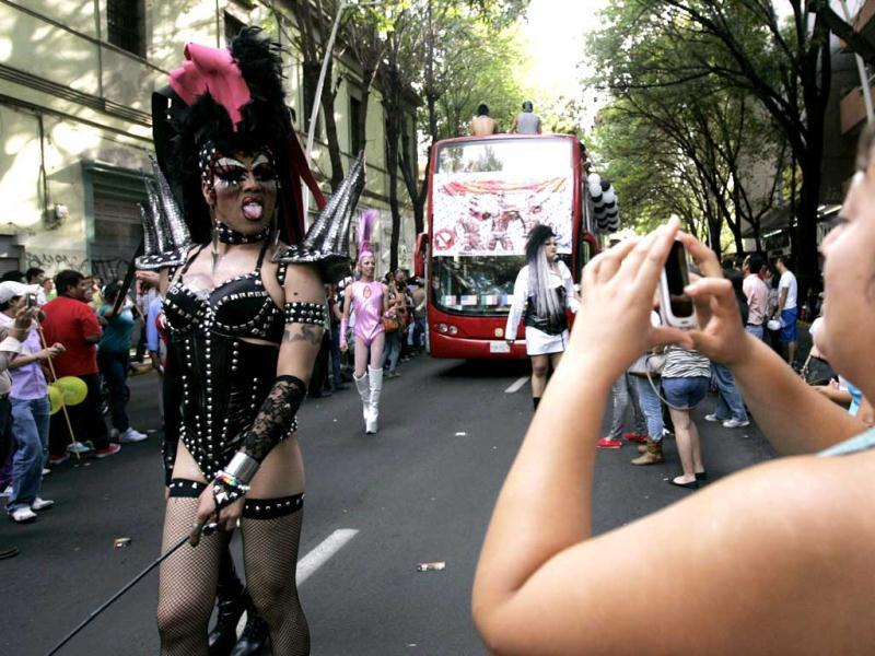 A woman takes photographs with her cell phone as a participant walks past during a parade celebrating sexual diversity in Guadalajara. Reuters/Alejandro Acosta
