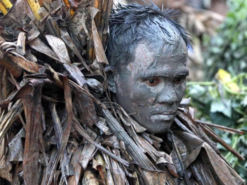 A devotee, covered with mud and dried banana leaves, attends a holy mass celebrating the feast day of their patron Saint John the Baptist in the village of Bibiclat, Nueva Ecija, north of Manila. Reuters/Erik De Castro
