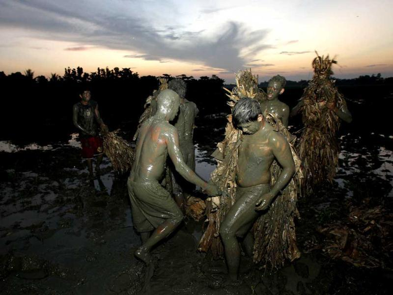 Devotees, covered with mud and dried banana leaves, take part in a religious ceremony celebrating the feast day of their Catholic patron Saint John the Baptist in the village of Bibiclat, Nueva Ecija, north of Manila. Reuters/Erik De Castro