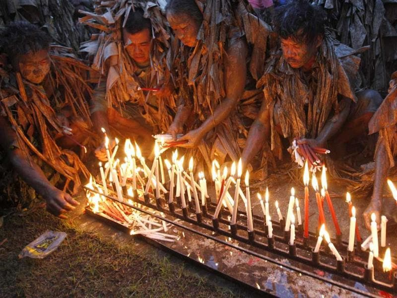 Devotees, covered with mud and dried banana leaves, light candles as they take part in a religious ceremony celebrating the feast day of their Catholic patron Saint John the Baptist in the village of Bibiclat, Nueva Ecija, north of Manila. Reuters/Erik De Castro