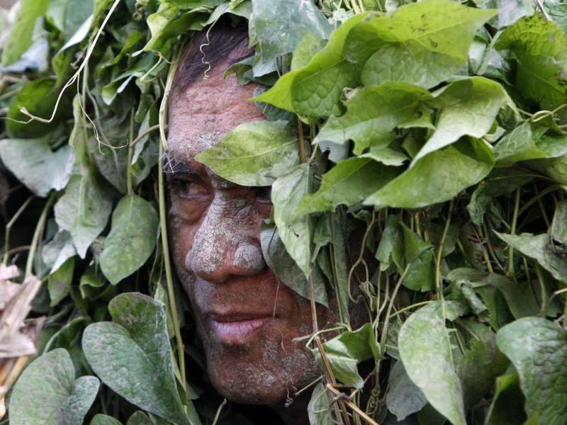 A devotee, covered with fresh leaves, attends a holy mass celebrating the feast day of their patron Saint John the Baptist in the village of Bibiclat, Nueva Ecija, north of Manila. Reuters/Erik De Castro