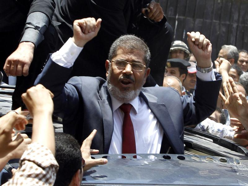 Mohamed Morsy of the Muslim Brotherhood waves to his supporters after casting his vote at a polling station in a school in Al-Sharqya, 60 km (37 miles) northeast of Cairo in this June 16, 2012 file photo. Reuters/Ahmed Jadallah