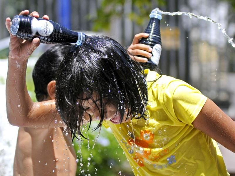 Children pour water on their heads to beat the heat in Sevilla. AFP/Cristina Quicler