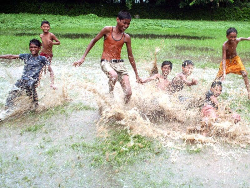 Children splash in water during monsoon rain which brought respite from scorching heat in Kolkata. UNI