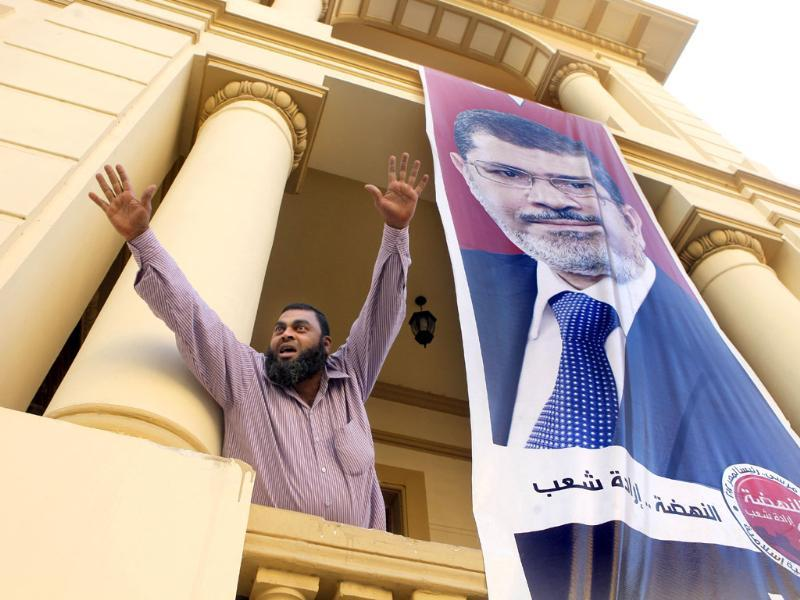 An Egyptian supporter of the Muslim Brotherhood's candidate, Mohammed Morsi, celebrates next to a giant campaign poster at his campaign headquarters in Cairo, Egypt.(AP Photo/Amr Nabil)