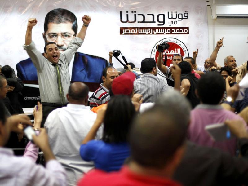 Supporters of the Muslim Brotherhood's presidential candidate Mohamed Morsy celebrate in front of his picture at his headquarters in Cairo. (Reuters/Suhaib Salem)