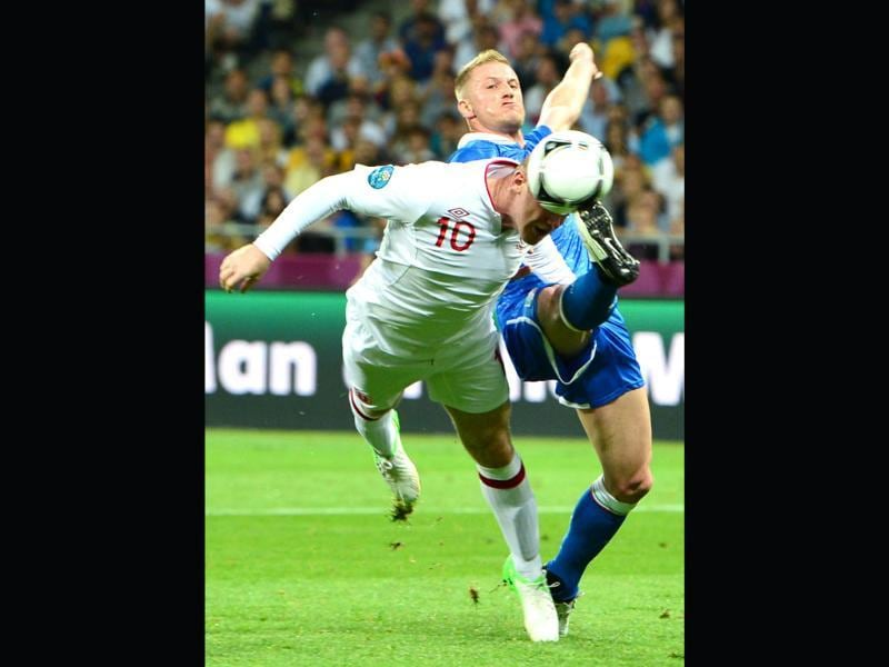 English forward Wayne Rooney (L) vies with Italian defender Ignazio Abate during the Euro 2012 football championships quarter-final match England vs Italy at the Olympic Stadium in Kiev. (AFP photo/Giuseppe Cacae)