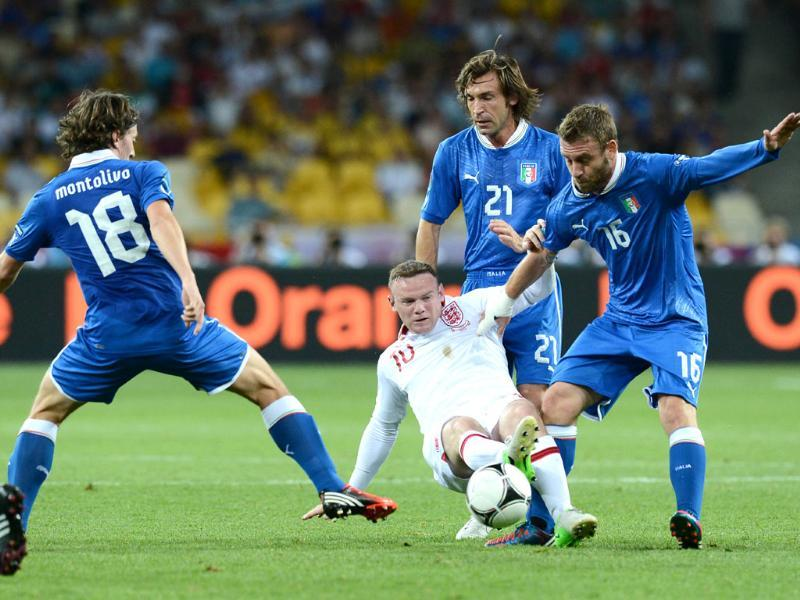 English forward Wayne Rooney (C) vies with Italian midfielder Daniele De Rossi (R) and Italian midfielder Andrea Pirlo and Italian midfielder Riccardo Montolivo (L) during the Euro 2012 football championships quarter-final match England vs Italy at the Olympic Stadium in Kiev. (AFP photo/Carl De Souza)