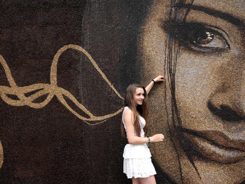 A girl looks at a coffee bean-made painting, challenging for a Guinness book record, in central Moscow. One painter and his five assistances made a 30 square meters painting within twelve days. AFP Photo/Kirill Kudryavtsev