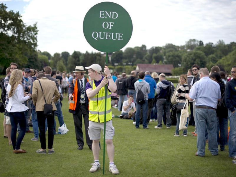 A steward holds a sign as tennis fans queue for tournament tickets to watch the action on the second day of the 2012 Wimbledon Championships tennis tournament at the All England Tennis Club in Wimbledon, southwest London. (AFP Photo)