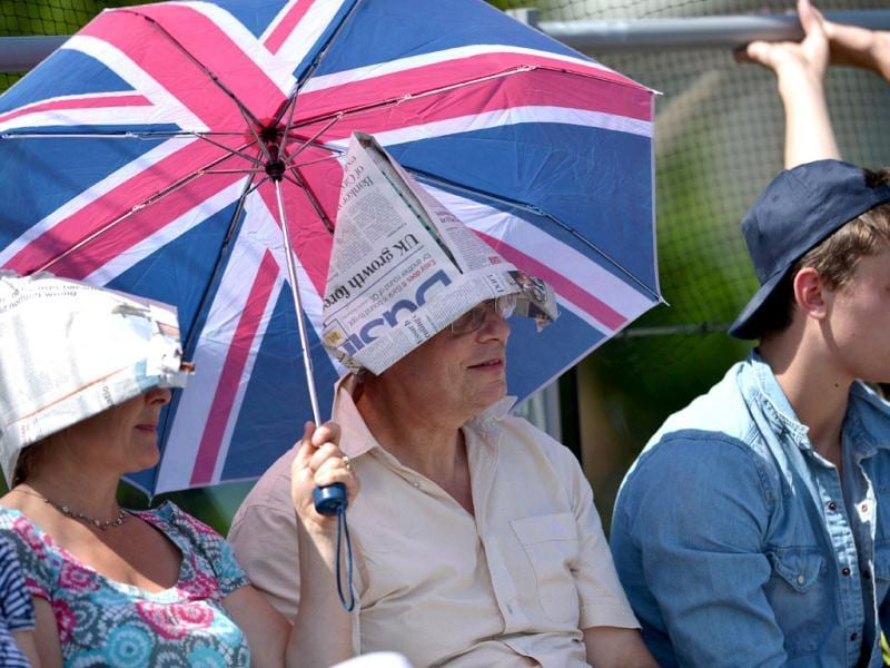 Supporters of Britain's Laura Robson shelter from the sun during her first round women's singles match against Italy's Francesca Schiavone on the second day of the 2012 Wimbledon Championships tennis tournament at the All England Tennis Club in Wimbledon, southwest London. (AFP Photo)