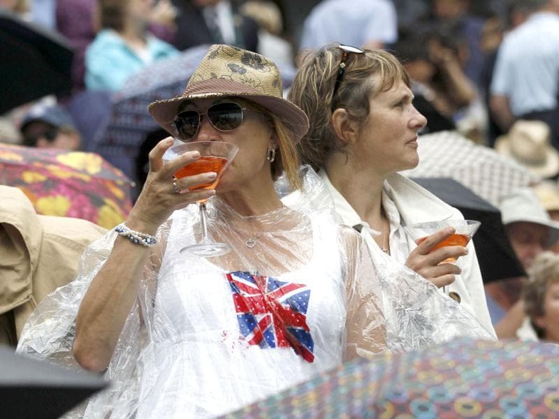 Fans try to keep dry on Centre Court during a spell of rain at the Wimbledon tennis championships in London. (Reuters)