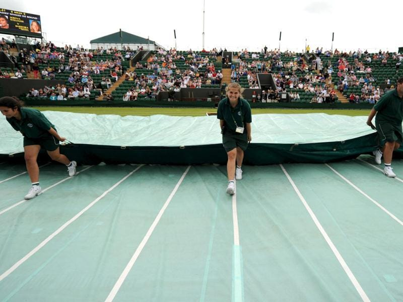 The protective rain covers are pulled off the grass by ground-staff on Court 2 on the second day of the 2012 Wimbledon Championships tennis tournament at the All England Tennis Club in Wimbledon, southwest London. (AFP Photo)