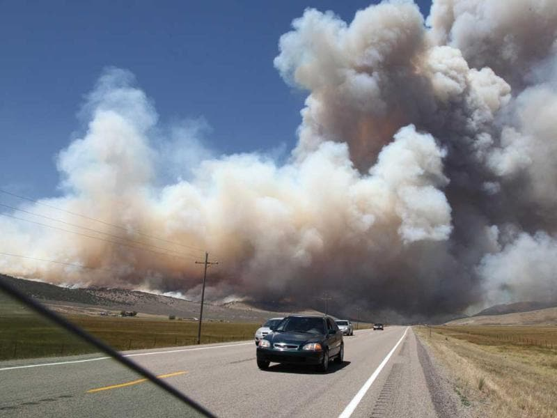 Towering columns of smoke cross US 89, after gusting winds whipped up a wildfiire that burned about 40,000 acres, destroying several dozen homes. AP/Lynn DeBruin
