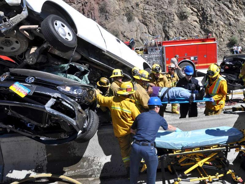 Firefighting paramedics remove an injured motorist after an accident at the site of a freeway pileup in northern Los Angeles County involving at least 19 vehicles which left at least 15 people injured, two of them critically. AP/Rick McClure