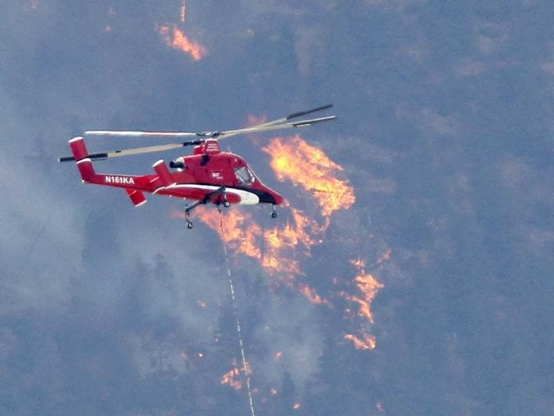 A firefighting helicopter approaches the Waldo Canyon fire west of Colorado Springs in Colorado. Reuters/Rick Wilking