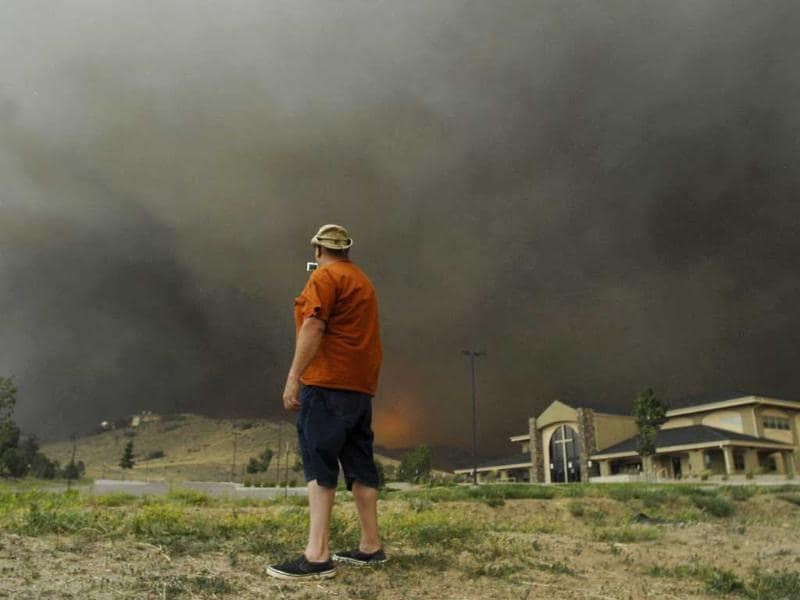 A man stops quickly to get some video before running away from approaching flames of the Waldo Canyon Fire as it raced down into western portions of Colorado Springs, leaving a trail of destruction and burning homes and buildings in its path. Heavily populated areas in the fire's path have been affected. AP/Bryan Oller